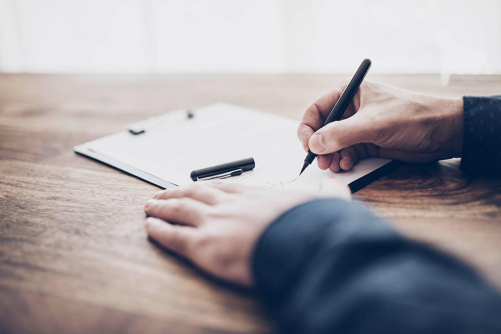 Bildausschnitt der Hände einer Person, die händisch auf einem Holztisch ein Formular ausfüllt.