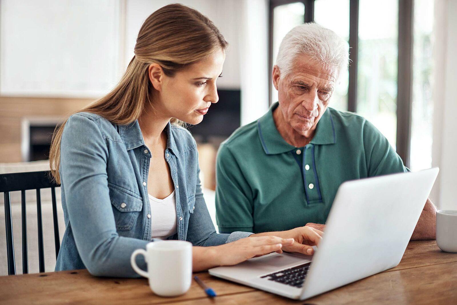 Bildausschnitt einer jungen Frau, die einen älteren Herrn am Laptop berät.