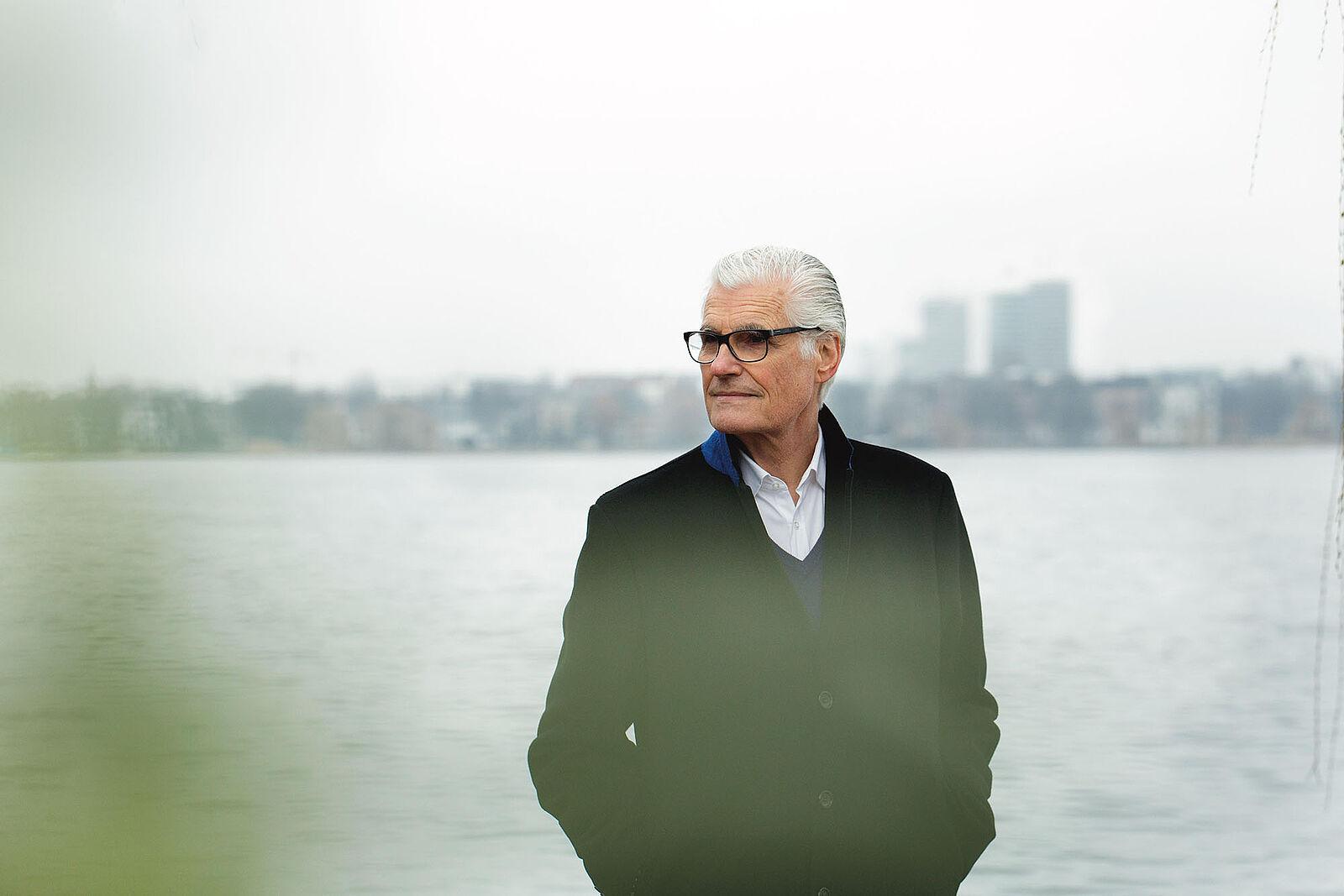 Bild von Schauspieler Sky Du Mont, der in einem schwarzen Mantel vor dem Rhein steht und in die Ferne blickt.