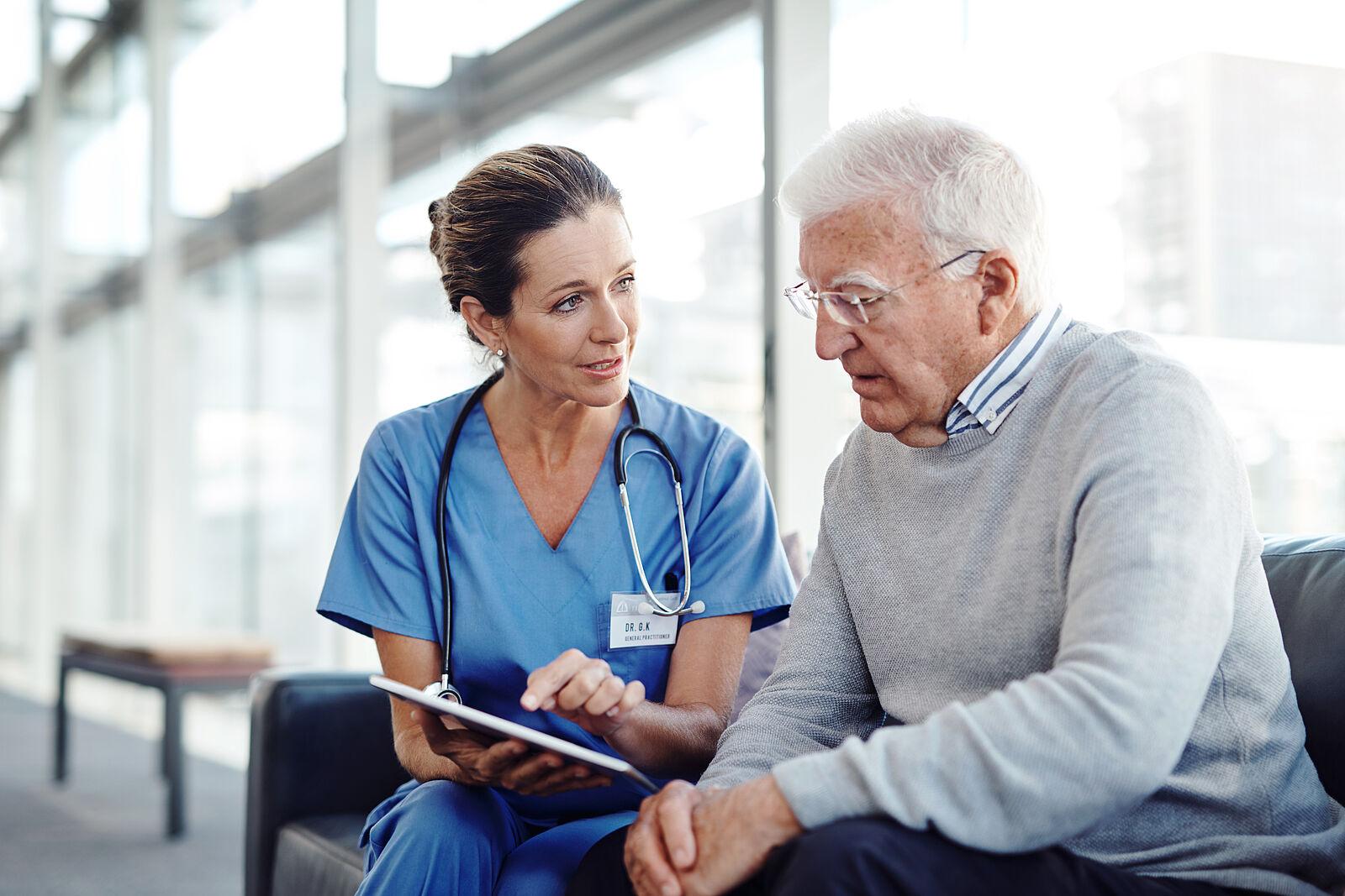 Älterer Herr wird durch medizinisches Personal im Wartebereich eines Krankenhauses beraten.