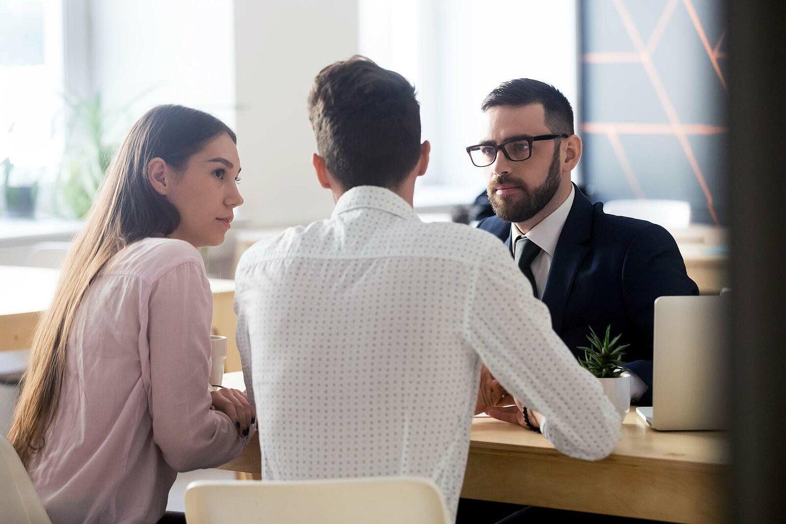 Junges Paar sitzt gemeinsam an einem massiven Holztisch und wird von einem Notar beraten.