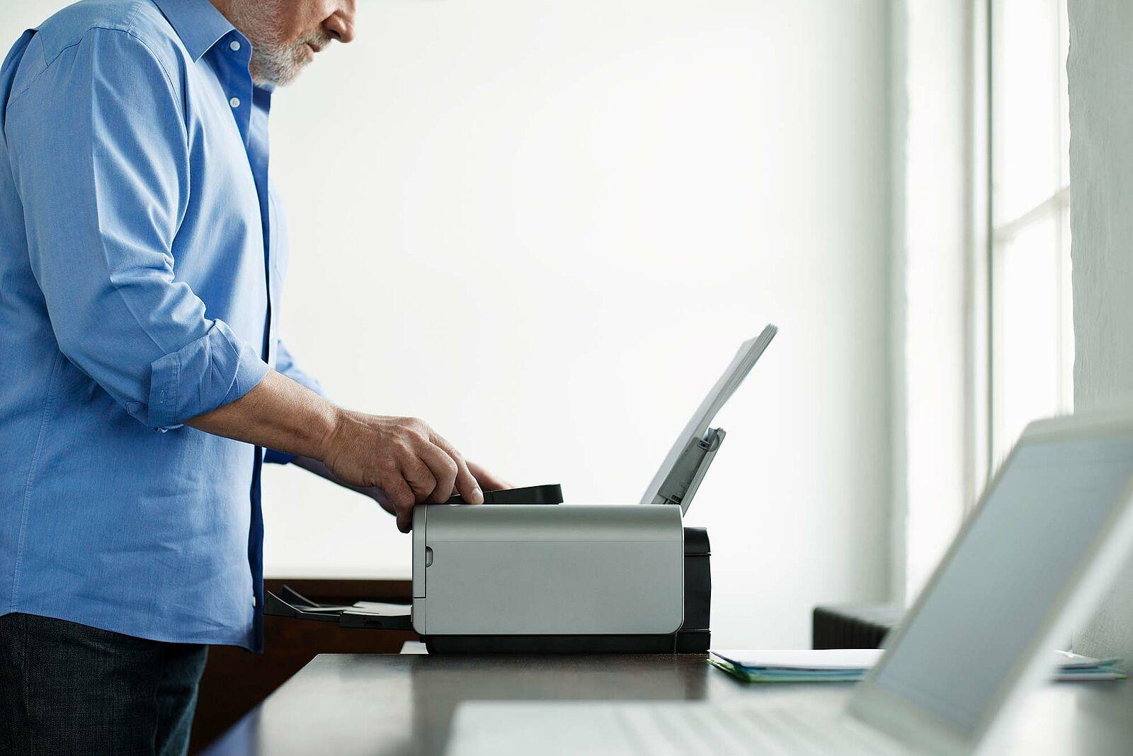 Bildausschnitt eines Mannes gekleidet im grauen Hemd der einen grauen Drucker betätigt.