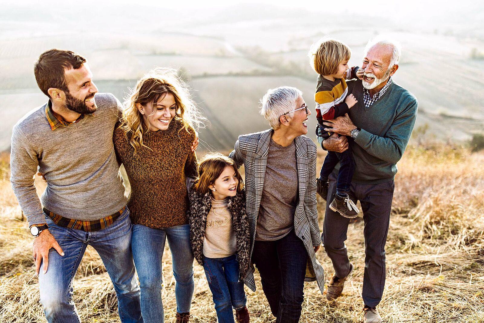 Bild einer glücklichen Drei-Generationen-Familie, die gemeinsam einen Berg hinaufspaziert sind, Felder und Wiesen im Hintergrund zu sehen.